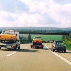 na obrazku widać trzy BMW 2002ti, dwa transportowane na lawetach, a jedno jadące o swoich siłach